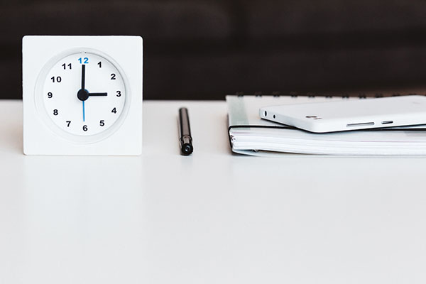 The right time to sell a business. Clock, Pen, notebook and smartphone on white table. Image by Public Co from Pixabay.